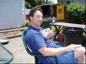 man sitting holding a chicken